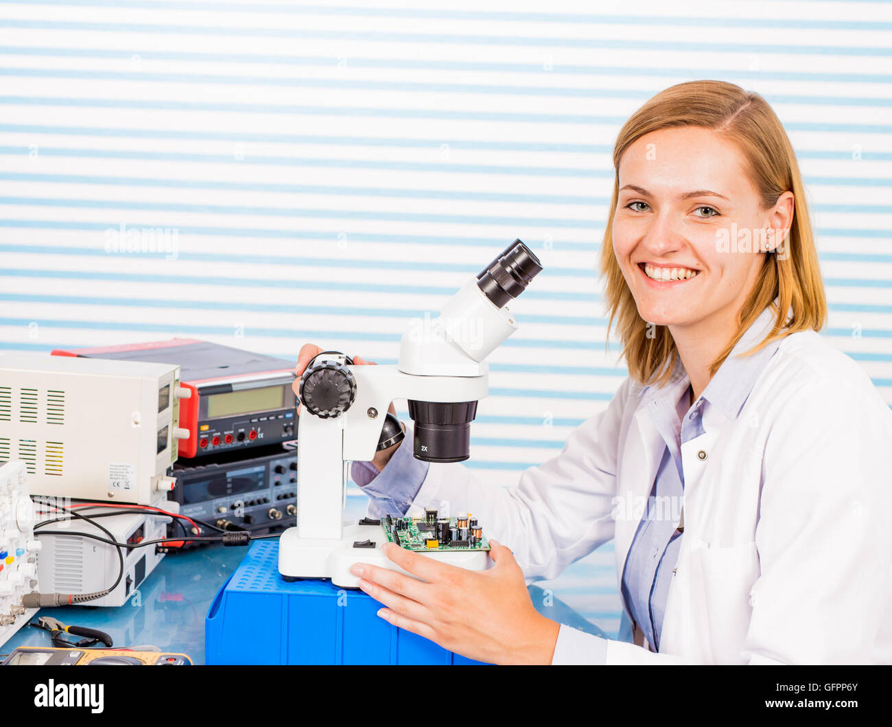 A young female researcher in a lab coat is peering into a microscope - Stock Image