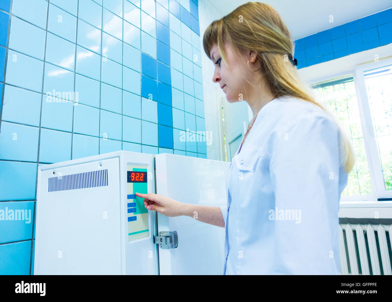 pharmaceutical factory woman worker operating autoclave for medicine drug steam sterilization at pharmacy industry - Stock Image