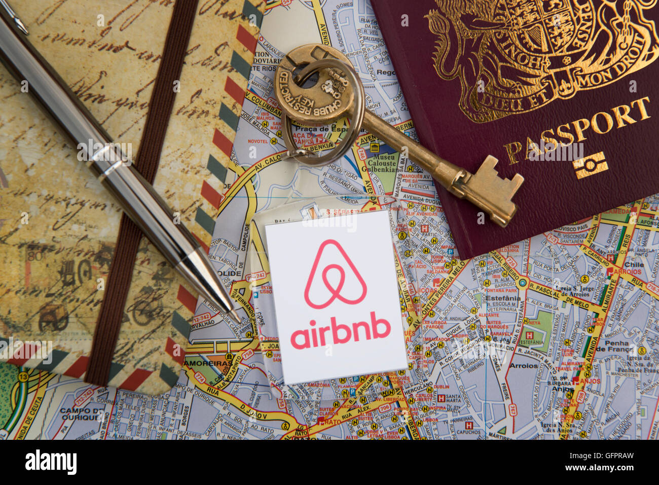 An Airbnb branded key fob with a British passport, travel journal, pen and city street map (Editorial use only). - Stock Image