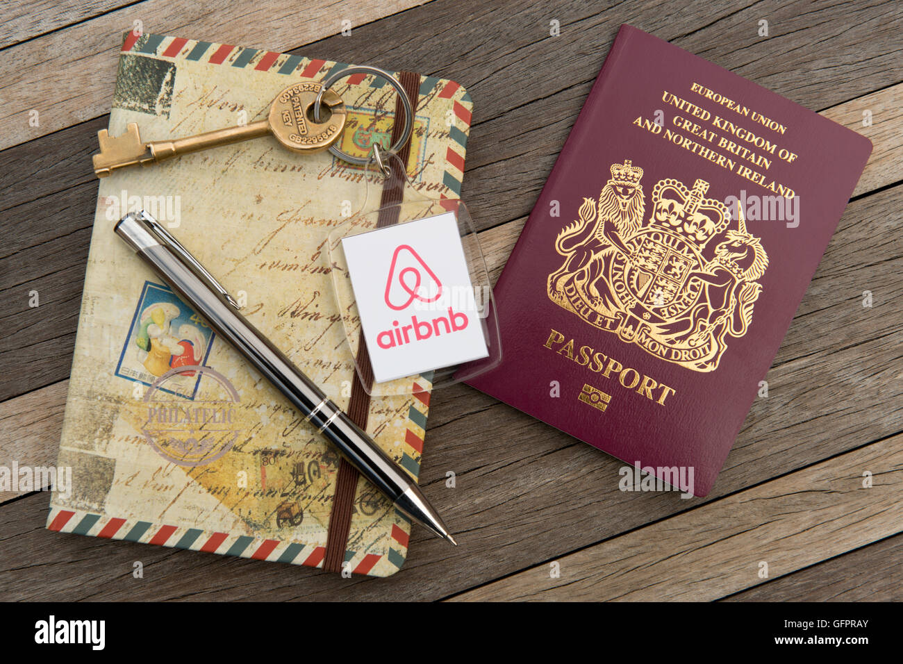 An Airbnb branded key fob along with a British passport, travel journal and pen, on a wooden table (Editorial use - Stock Image