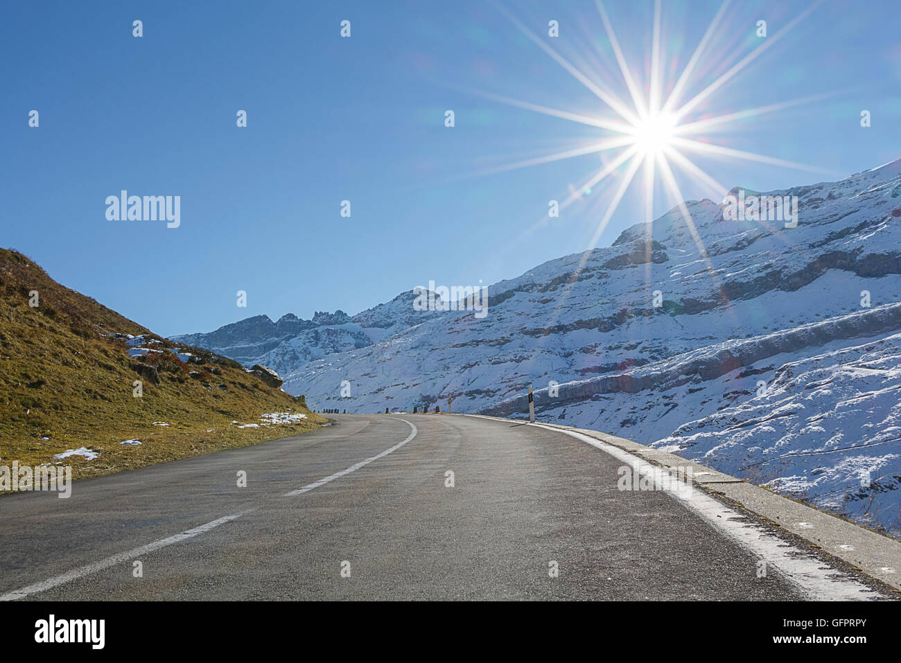 A mountain Road with the sun directly ahead. Could be used to show driving holiday or adventure - Stock Image