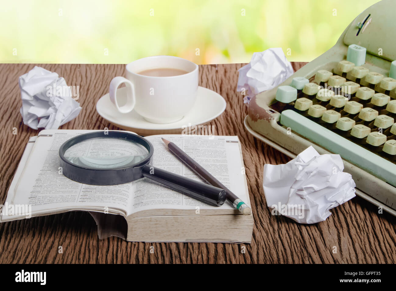 The thai dictionary consider under a magnifier on writer's desk with crumpled sheets around - Stock Image