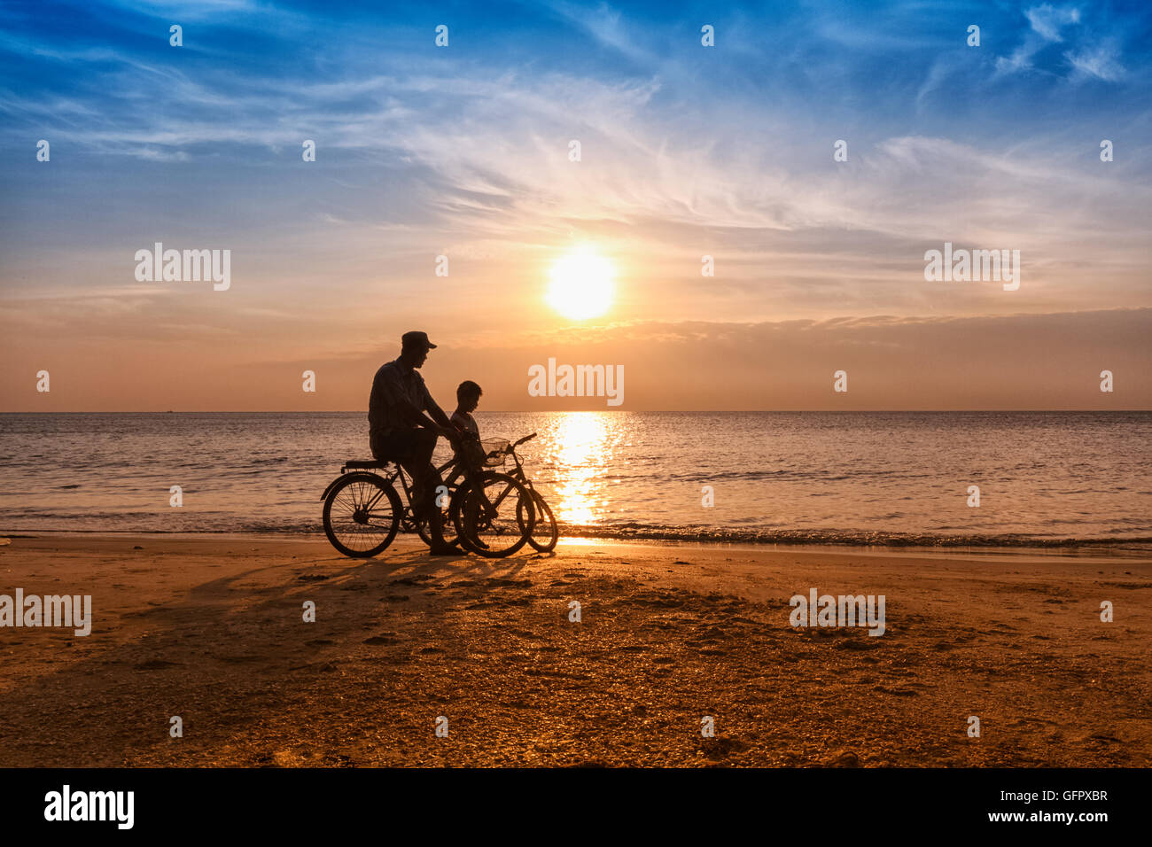 Biker family silhouette father and son on the beach in the sun rise - Stock Image
