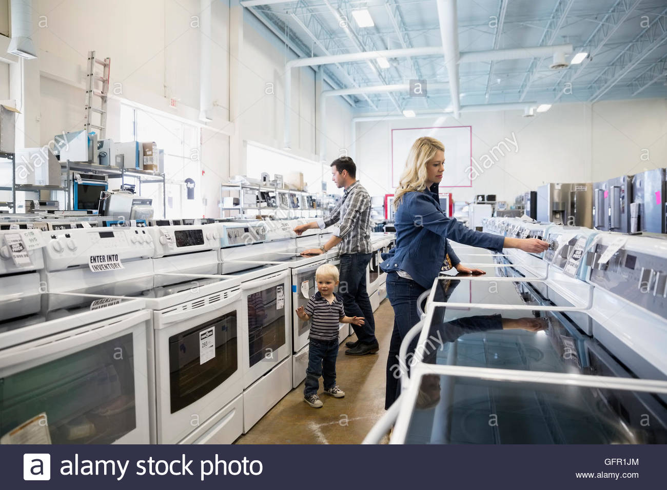 Young family shopping for stoves in appliance store - Stock Image