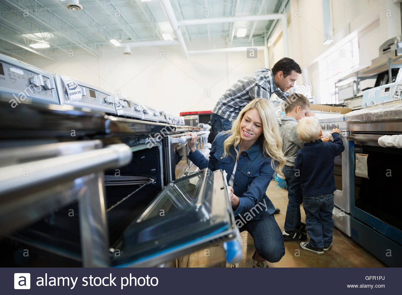 Young family shopping for ovens in appliance store - Stock Image