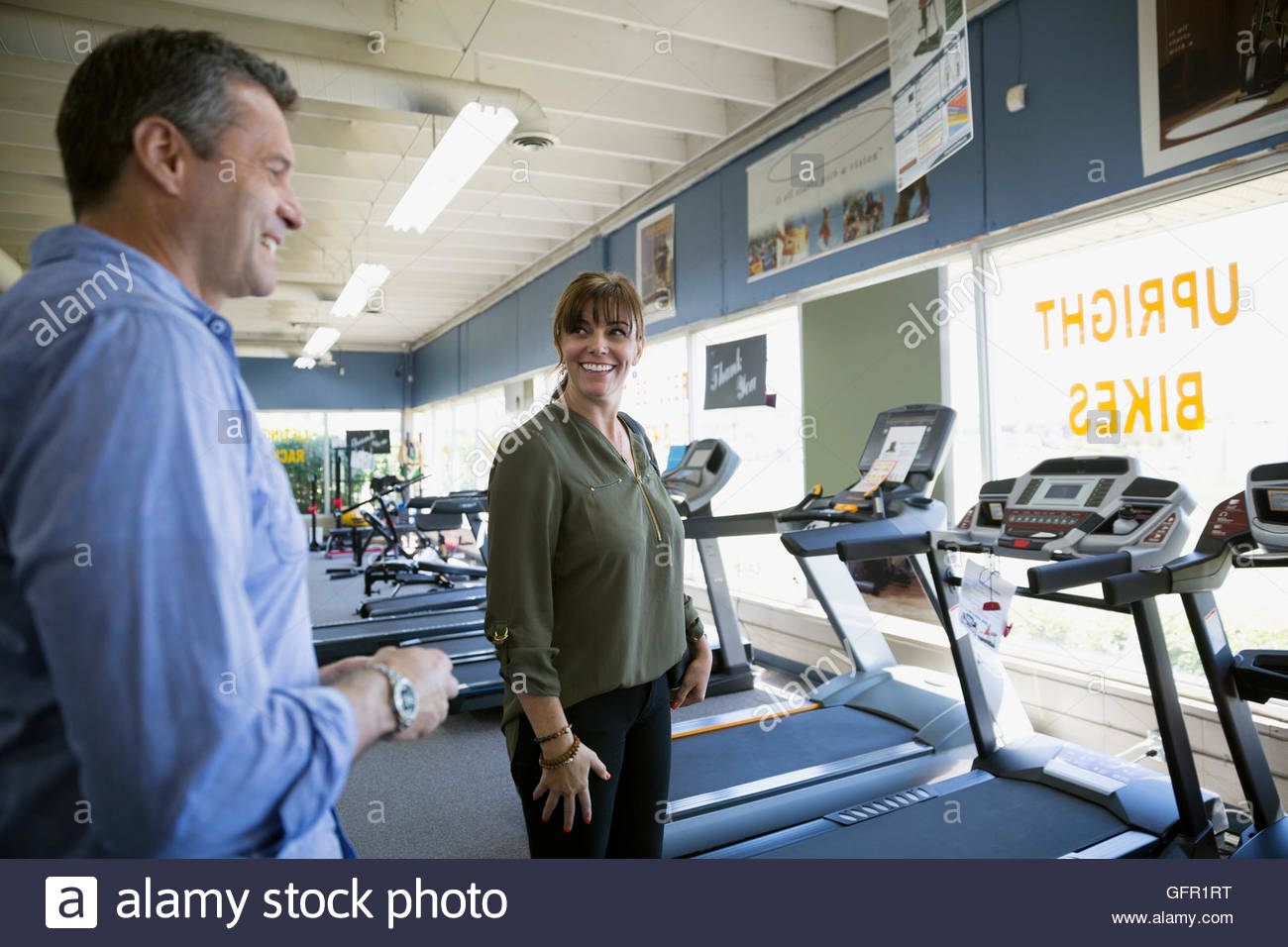 Couple browsing treadmills in home gym equipment store - Stock Image