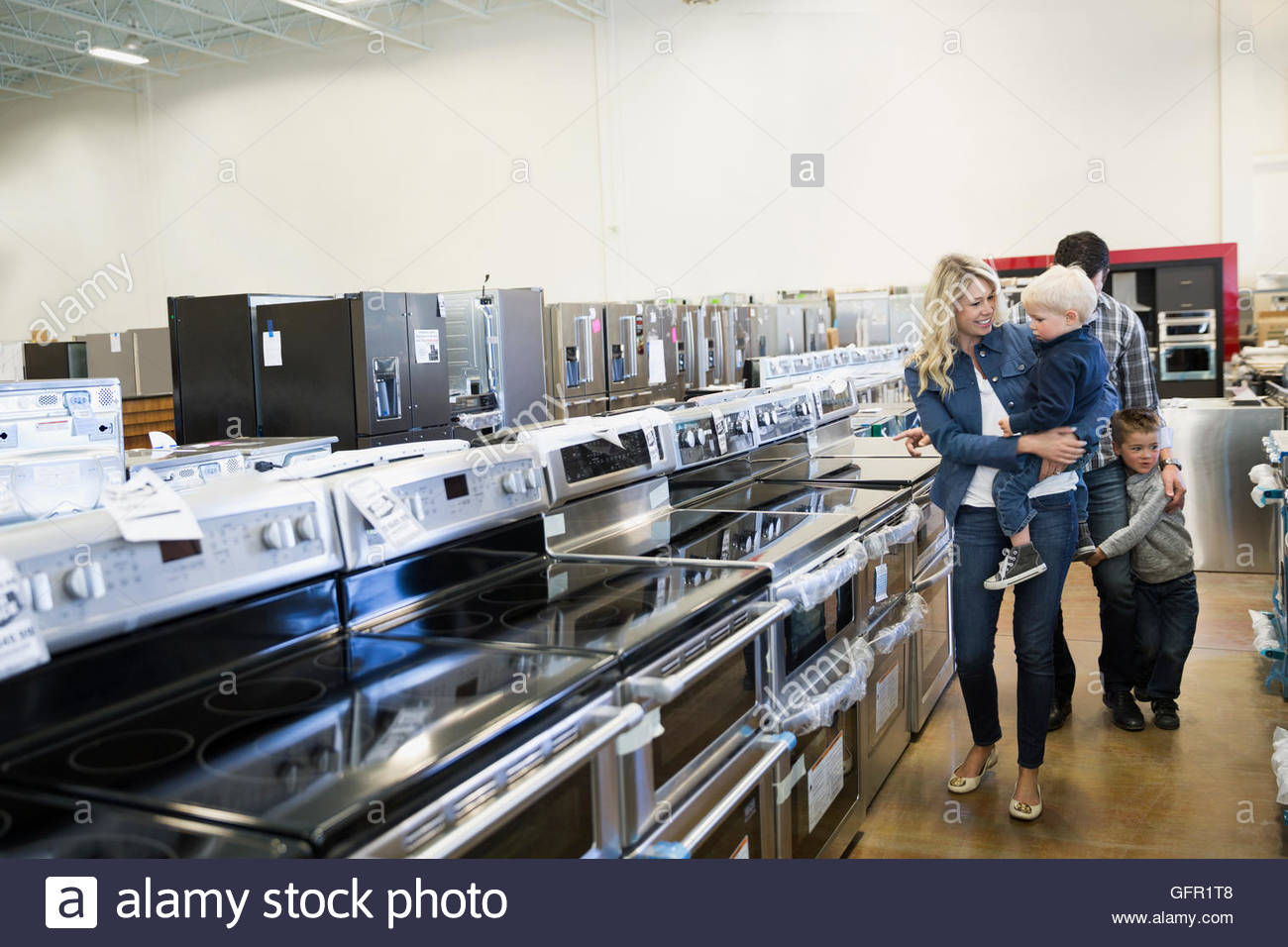 Young family shopping in appliance store - Stock Image