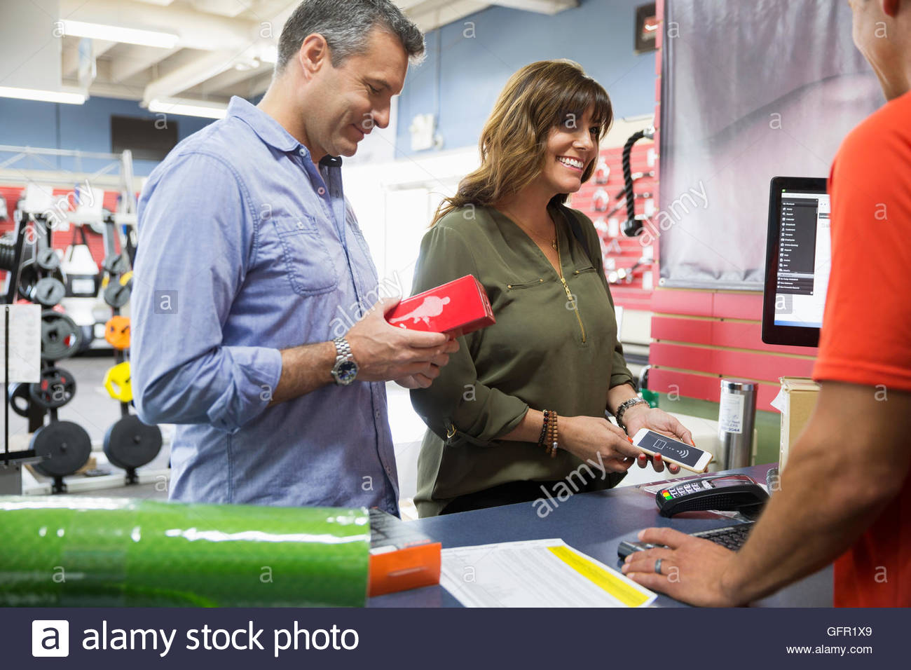 Couple paying using contactless payment in home gym equipment store - Stock Image