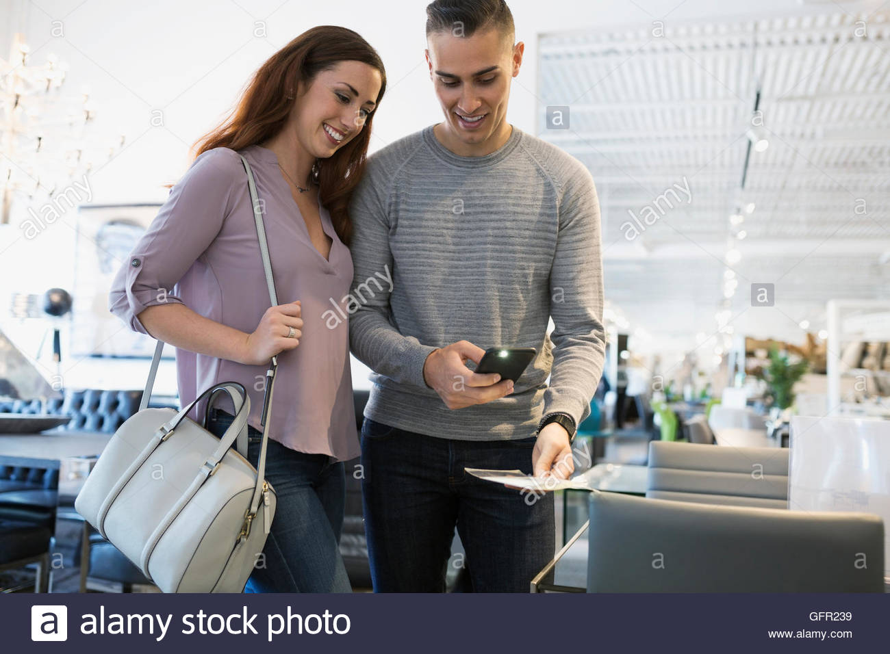 Couple photographing price tag with camera phone in home furnishings store - Stock Image