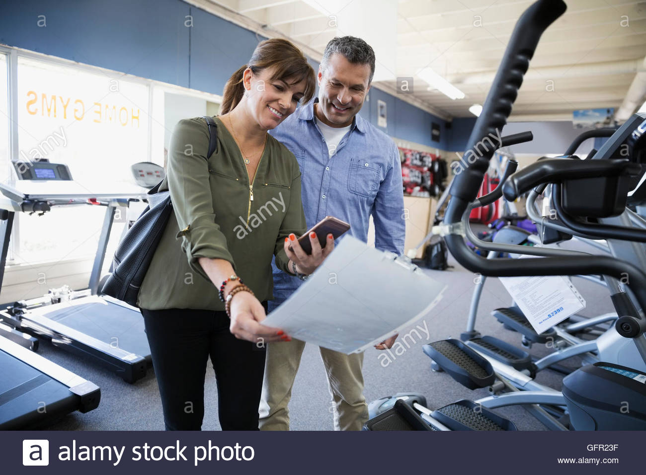 Couple browsing information sign on cardio machine at home gym equipment store - Stock Image