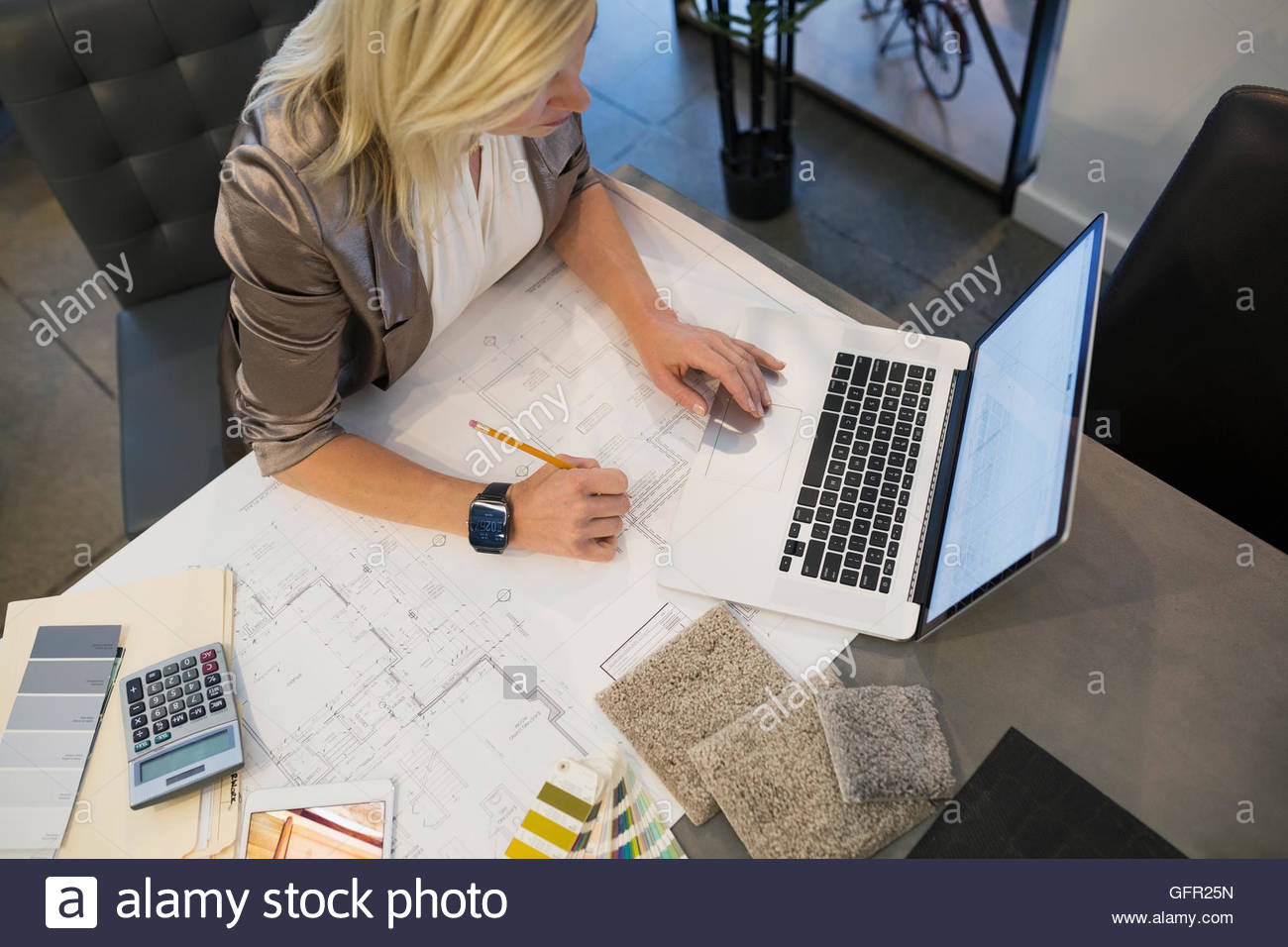 Interior designer with blueprints and swatches working at laptop - Stock Image