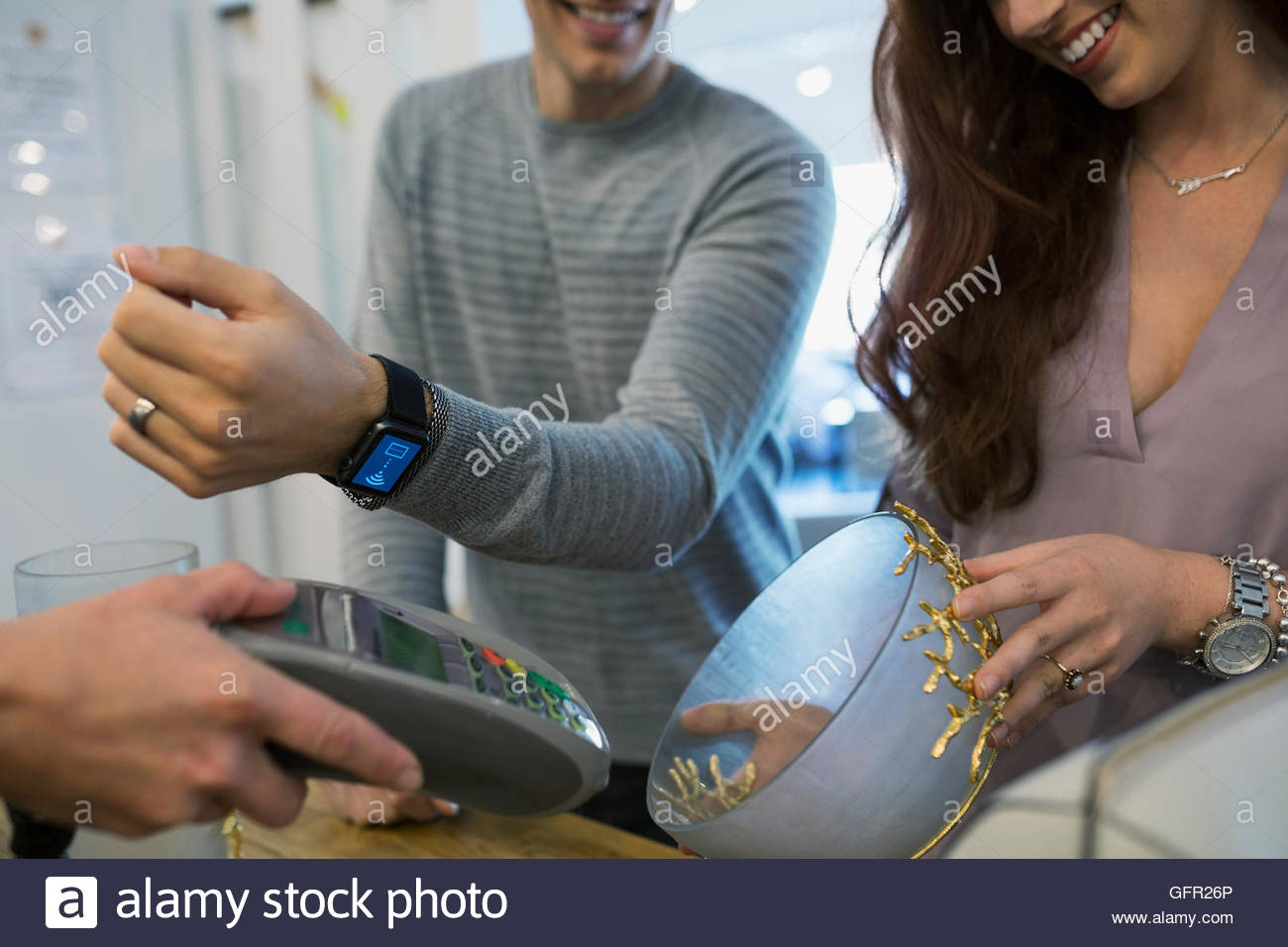 Man paying using smart watch contactless payment at home furnishings store - Stock Image