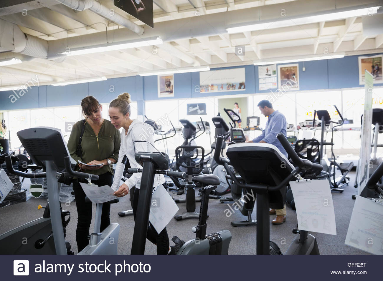 Saleswoman helping woman browsing cardio machines at home gym equipment store - Stock Image