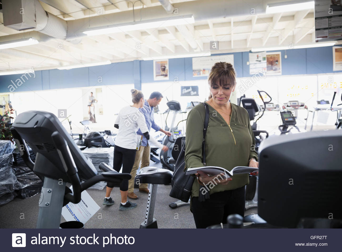 Woman reading information booklet on cardio machine at home gym