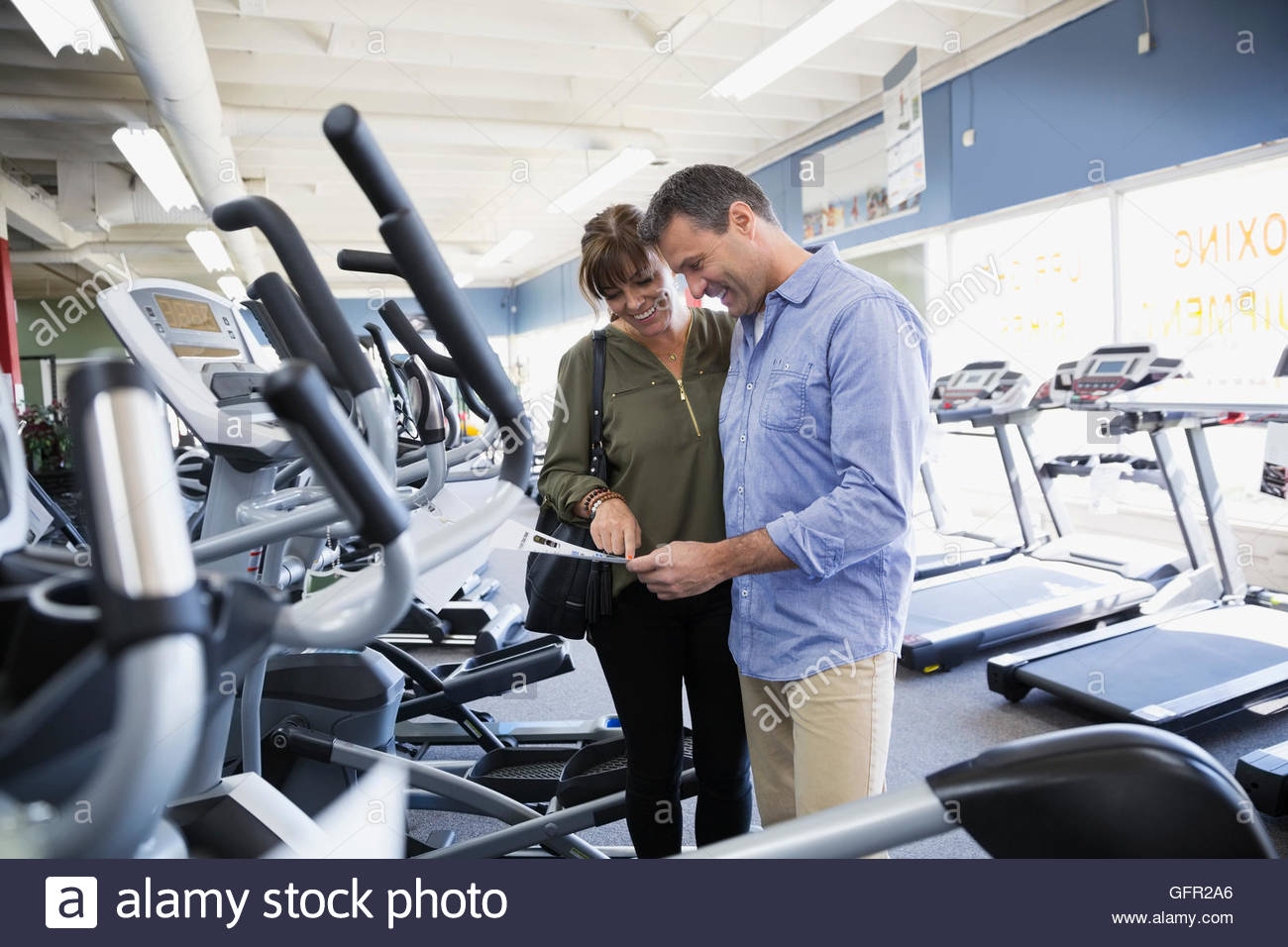 Couple looking at price tag on home gym cardio equipment in store - Stock Image