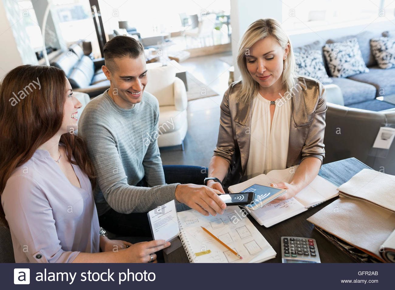 Couple paying using contactless payment in home furnishings store - Stock Image