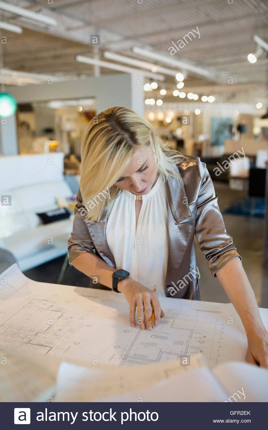 Interior designer reviewing blueprints in home furnishings store - Stock Image