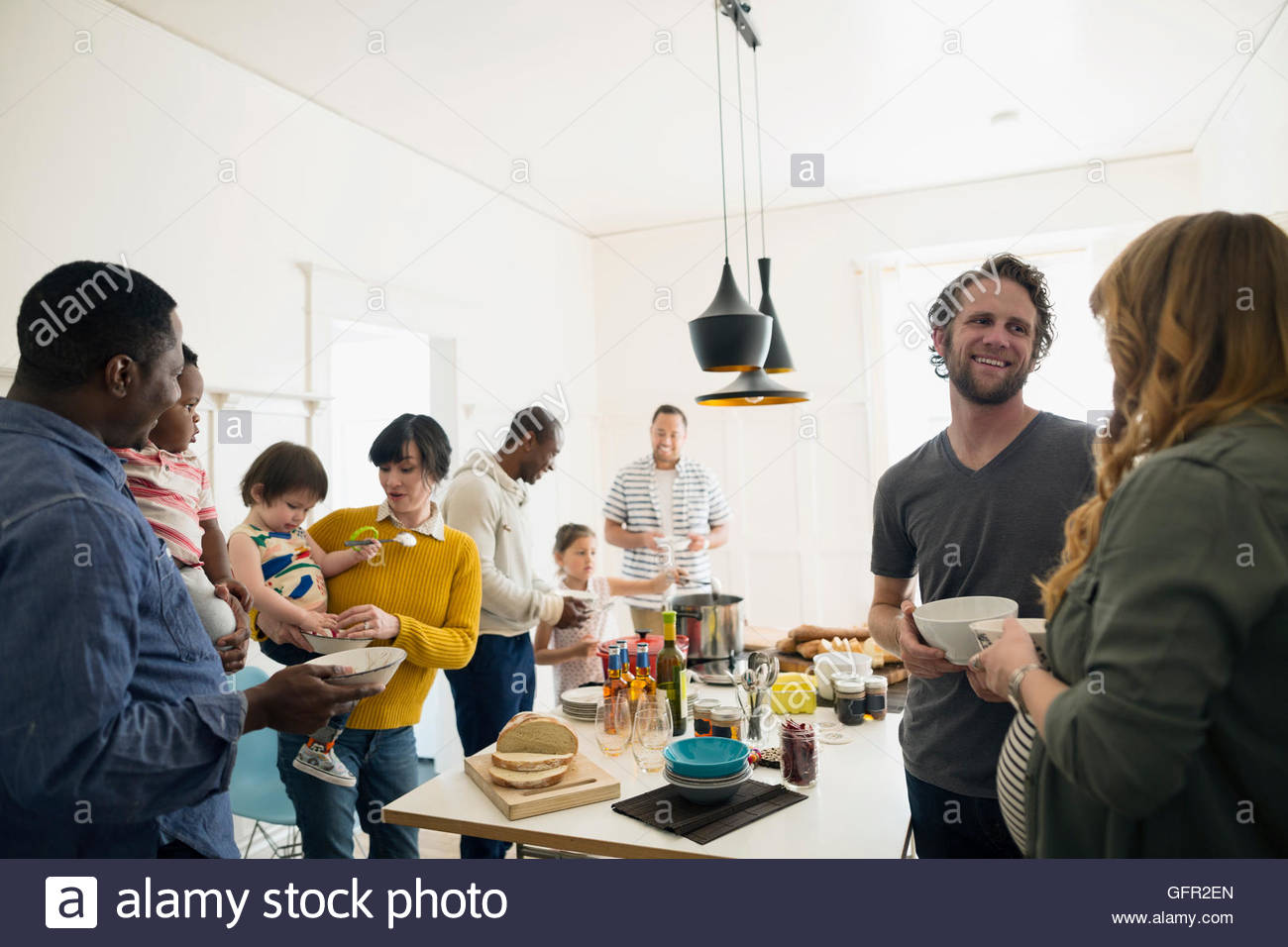 Families talking enjoying lunch buffet in dining room - Stock Image