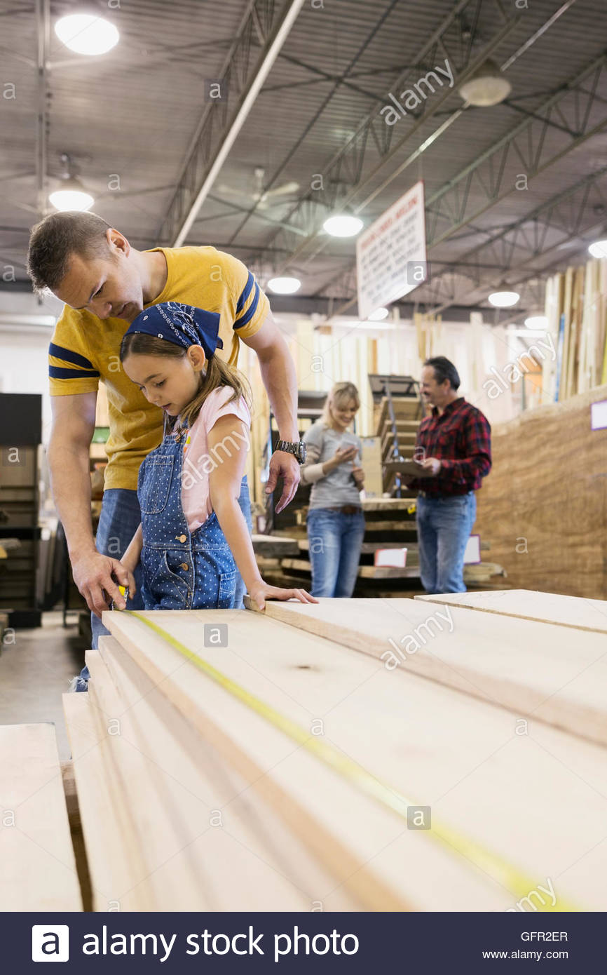 Father and daughter measuring wood planks in home improvement store - Stock Image