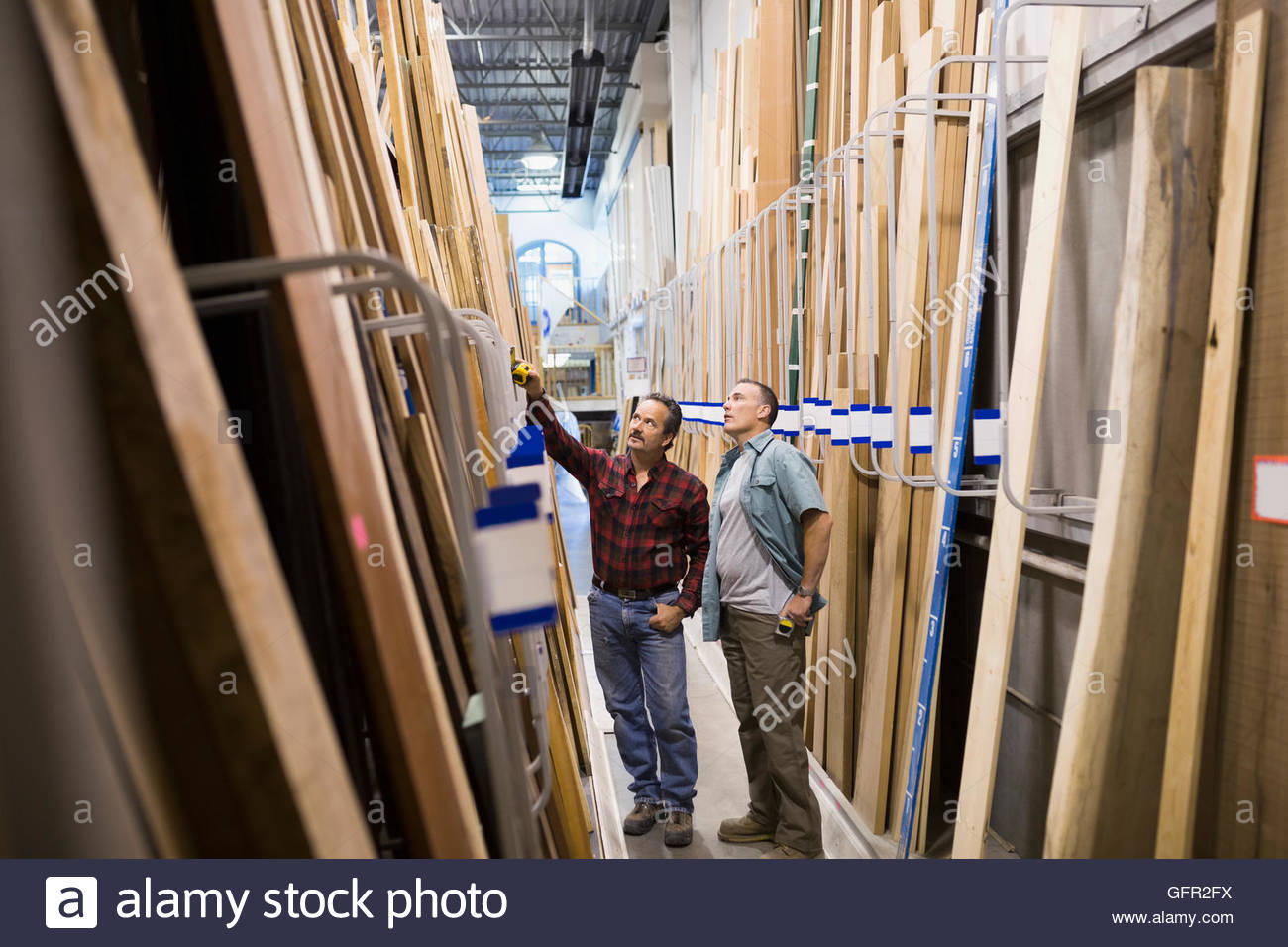 Men discussing wood at home improvement store - Stock Image