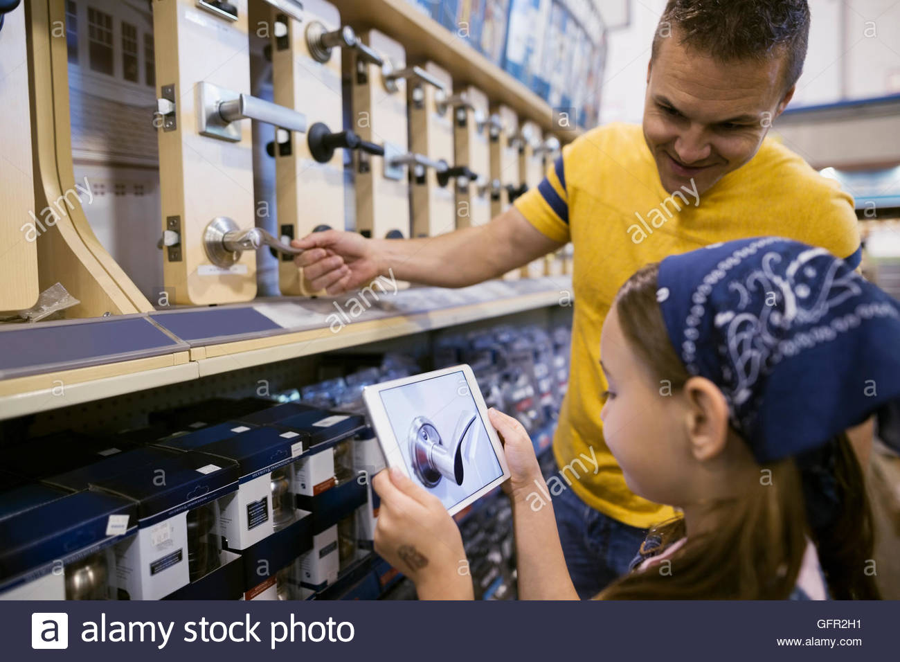 Father and daughter with digital tablet shopping for drawer pulls in home improvement store - Stock Image