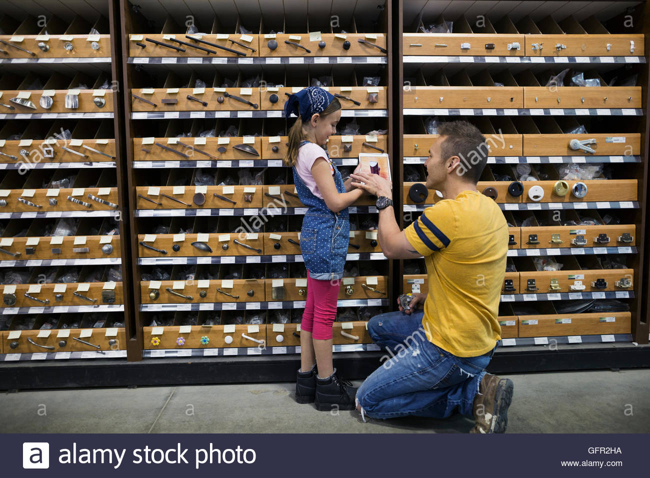 Father and daughter shopping for drawer pulls in home improvement store - Stock Image