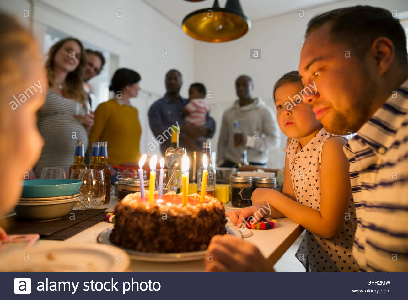 Father and daughters with birthday cake candles at party - Stock Image