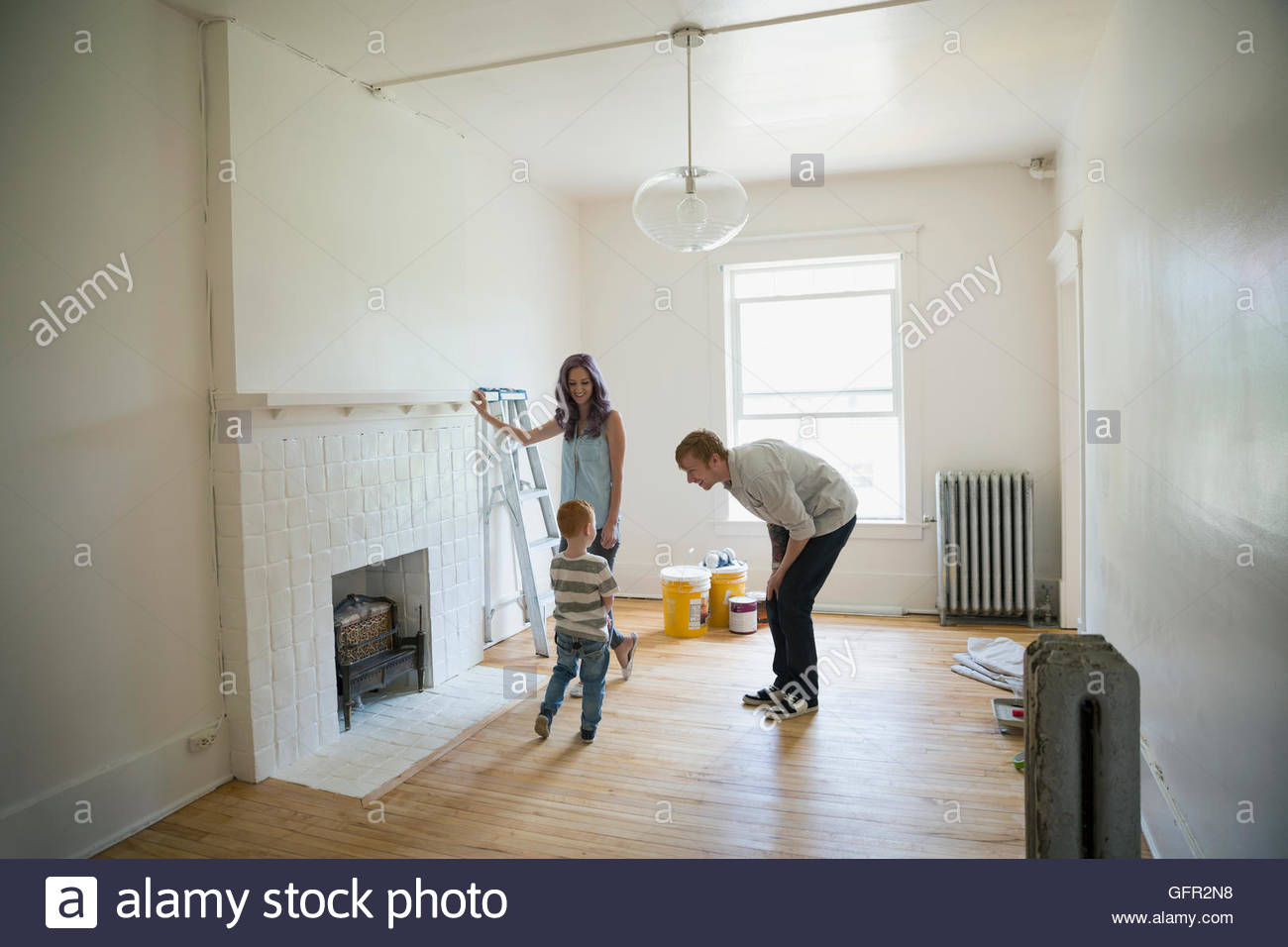 Young family in living room of empty new house - Stock Image