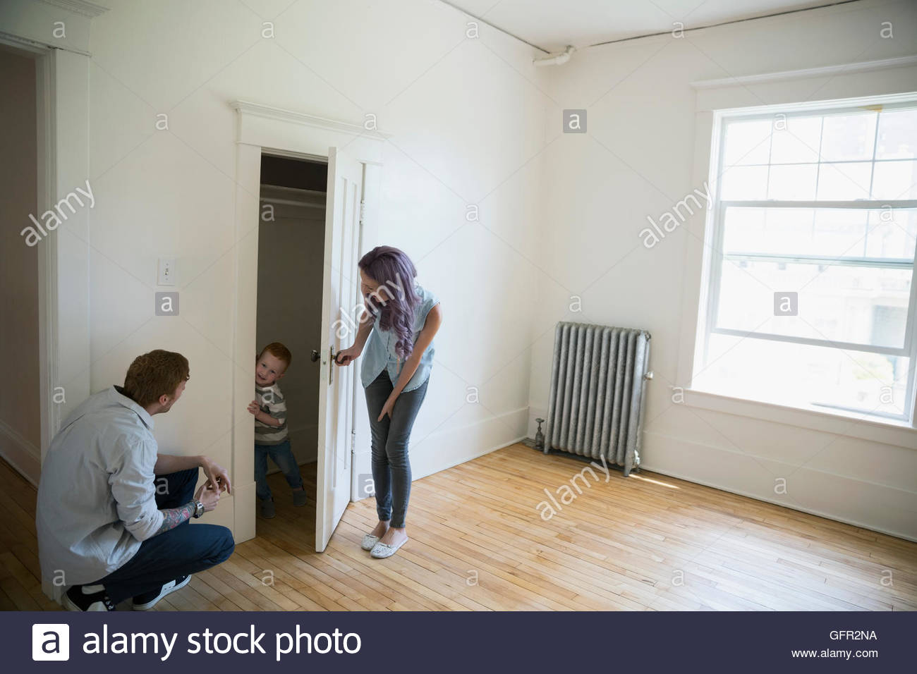 Playful young family in empty new house - Stock Image