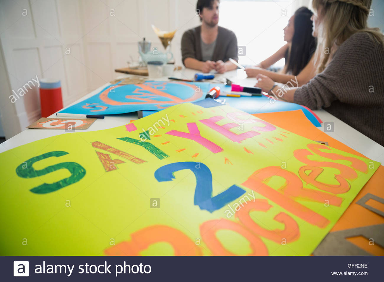 Young activists making posters in dining room - Stock Image
