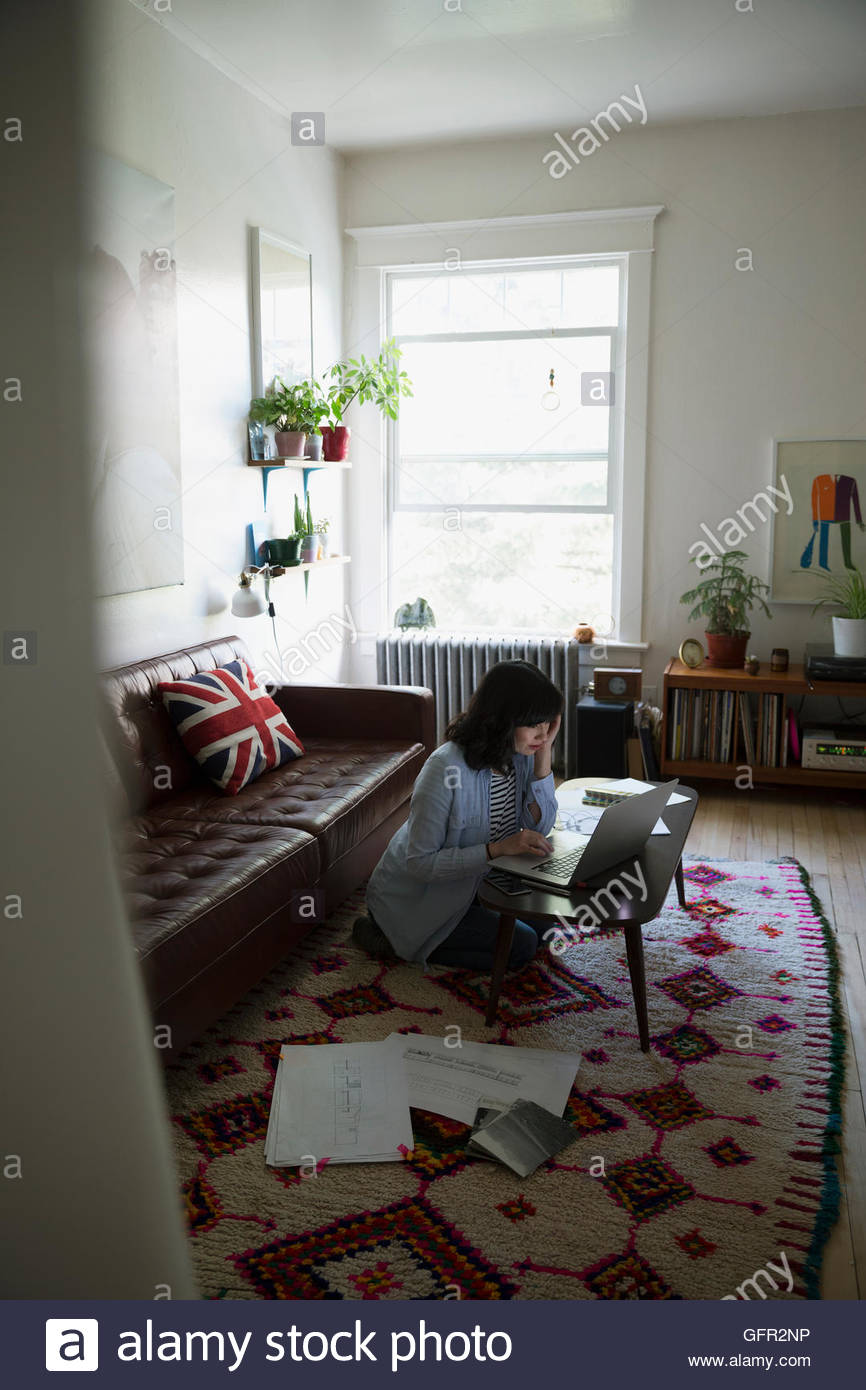 Female architect using laptop in living room - Stock Image