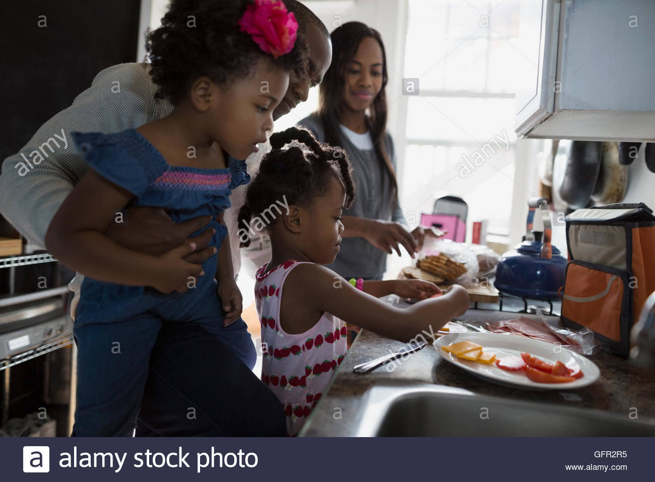 Young family making school lunches in kitchen - Stock Image