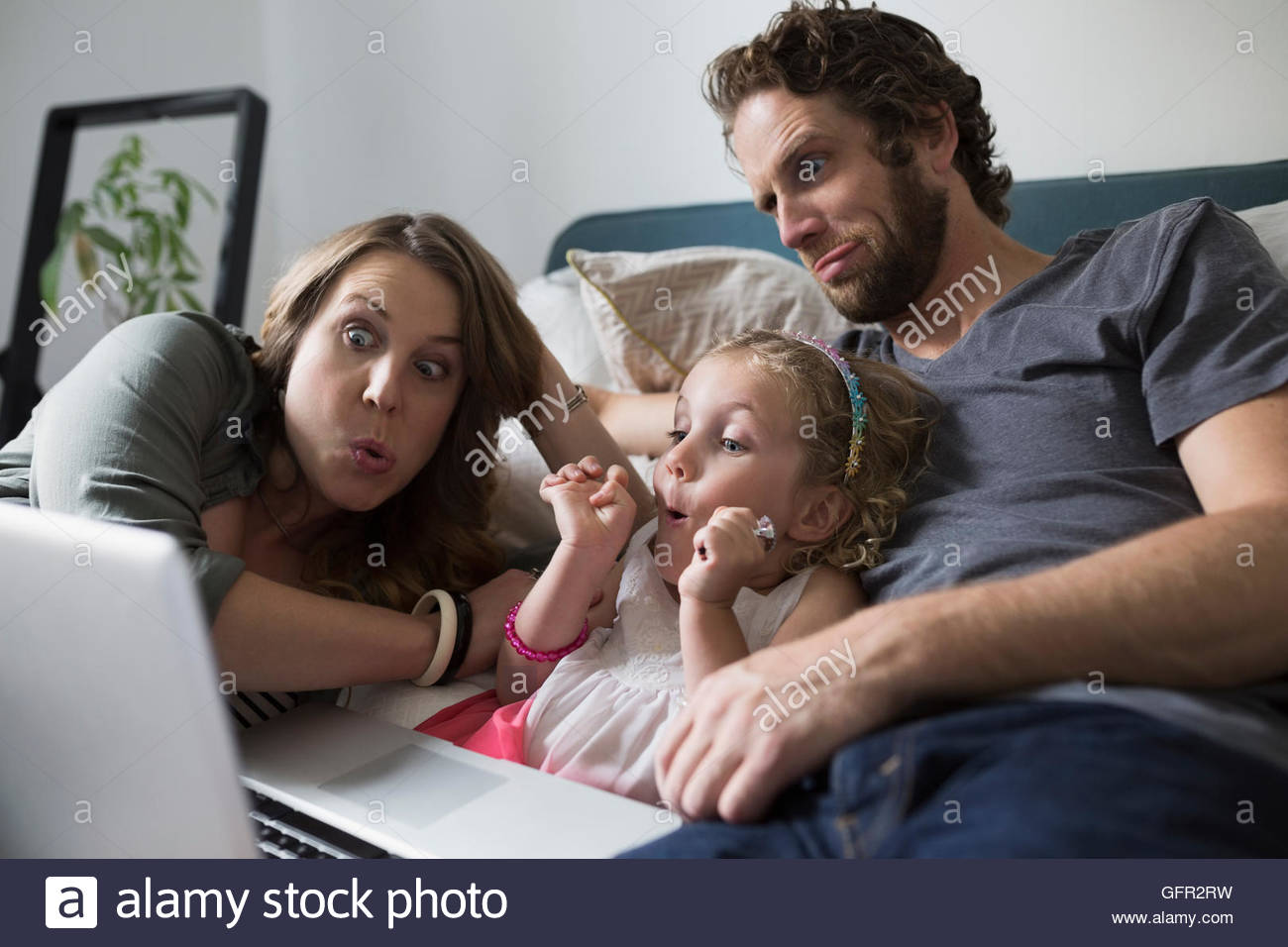 Young family making faces video chatting with laptop on bed - Stock Image