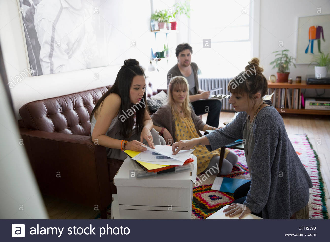 Young activists meeting and planning in living room - Stock Image