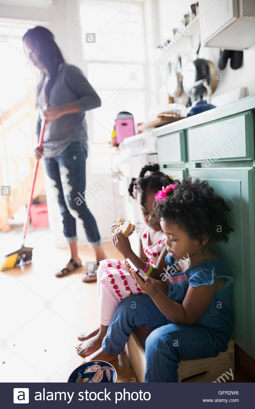 Girls eating sandwich and using smart phone in kitchen - Stock Image