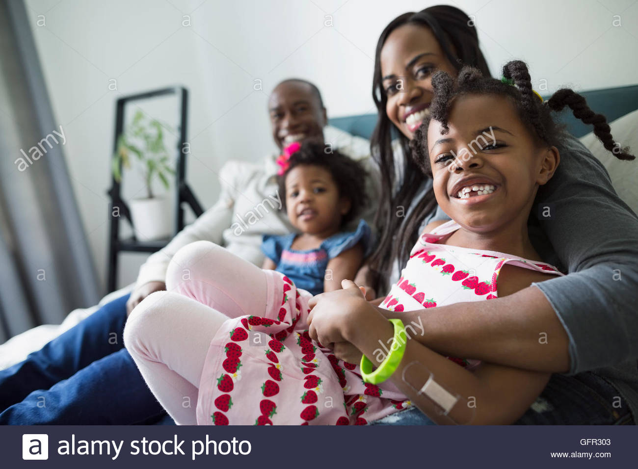 Portrait smiling young family in bedroom - Stock Image