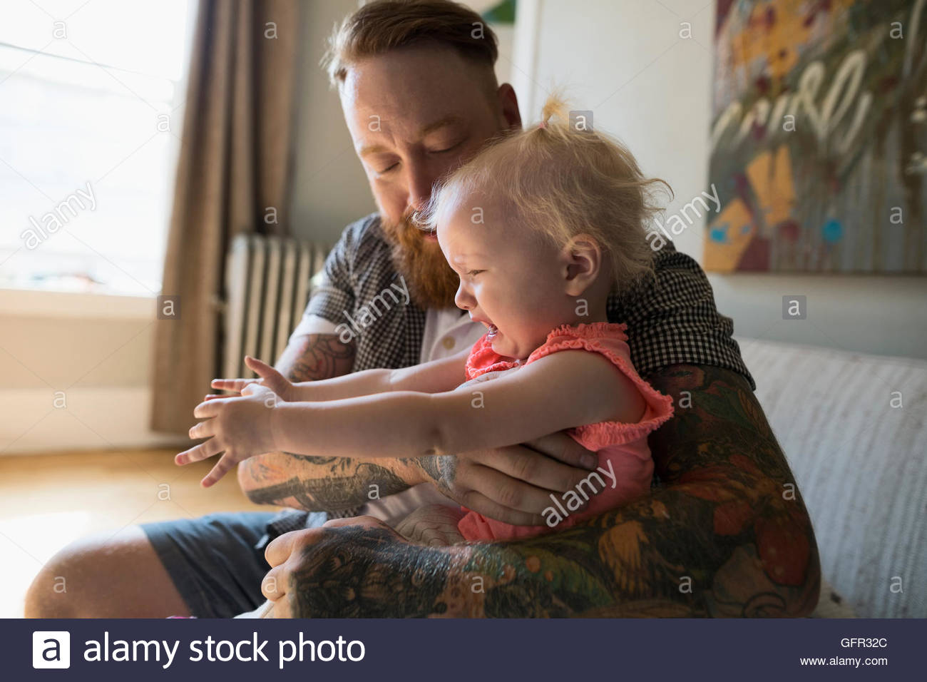 Father with tattoos holding crying daughter - Stock Image