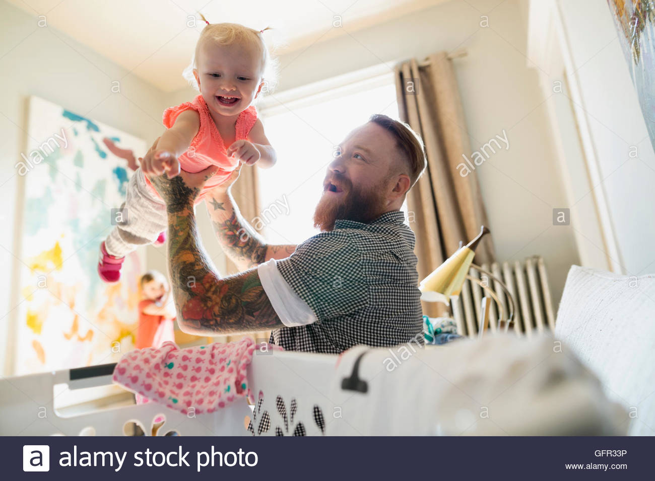 Father playfully lifting daughter over laundry basket - Stock Image
