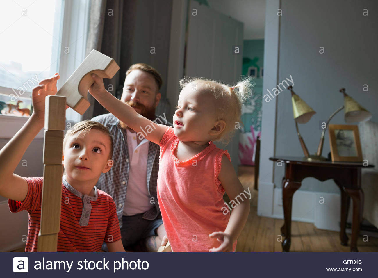 Father and children playing stacking wood blocks - Stock Image