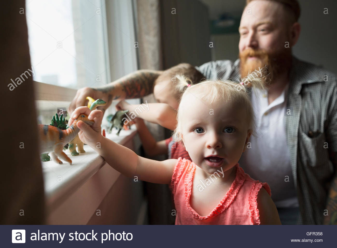 Portrait daughter and father playing with toy dinosaurs at windowsill Stock Photo