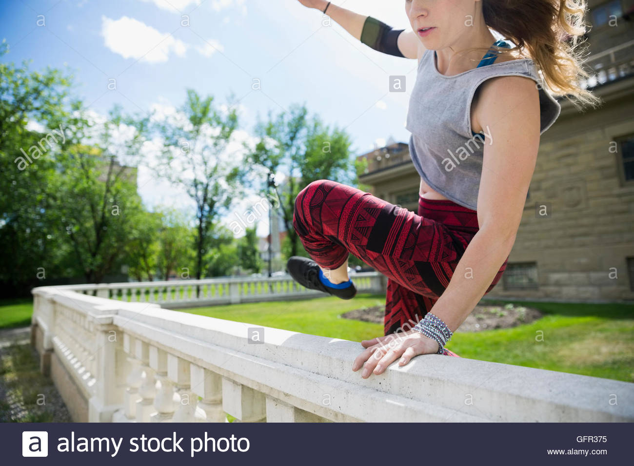Young woman doing parkour jumping over railing - Stock Image