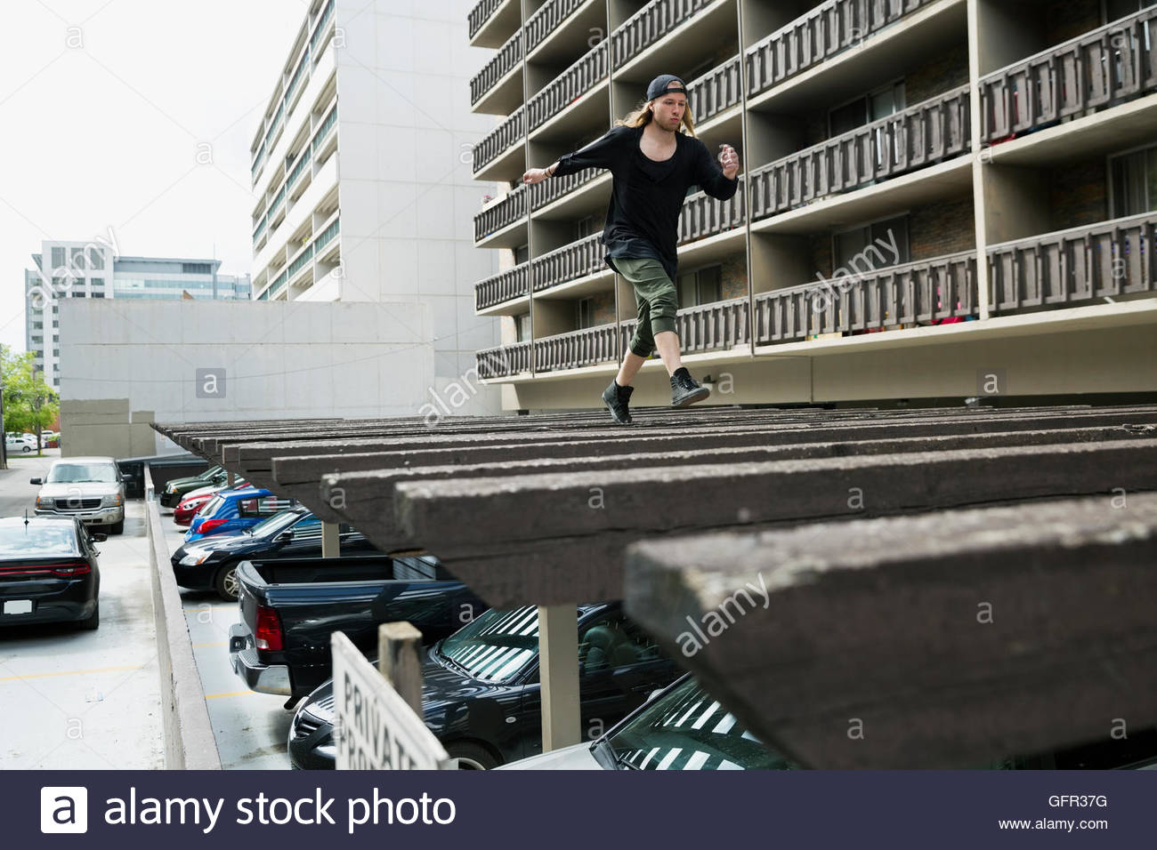 Young man free running on carport roof below urban apartment buildings - Stock Image