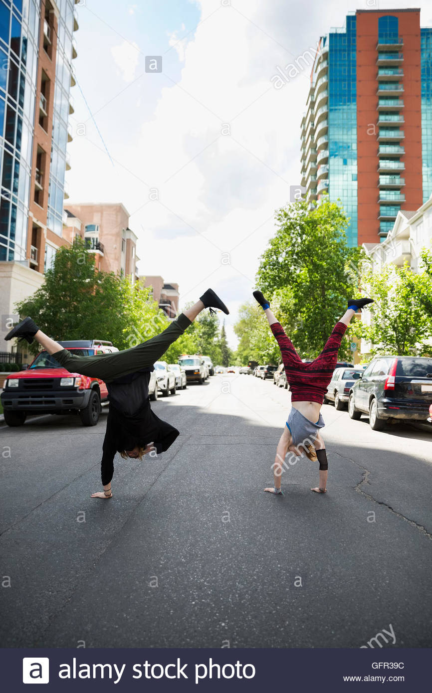 Cool young man and woman doing handstands in urban street - Stock Image