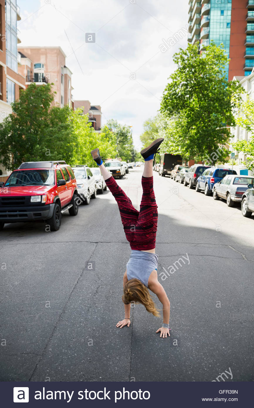 Cool young woman doing handstand in urban street - Stock Image