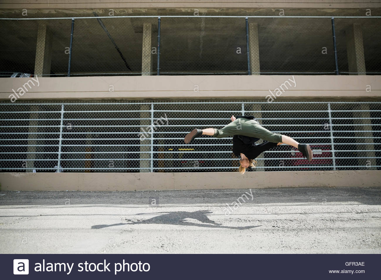 Young man doing parkour against fence in urban alley - Stock Image
