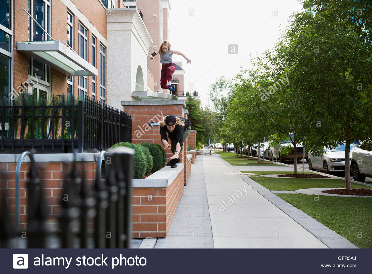Young woman doing free running parkour along ledges - Stock Image