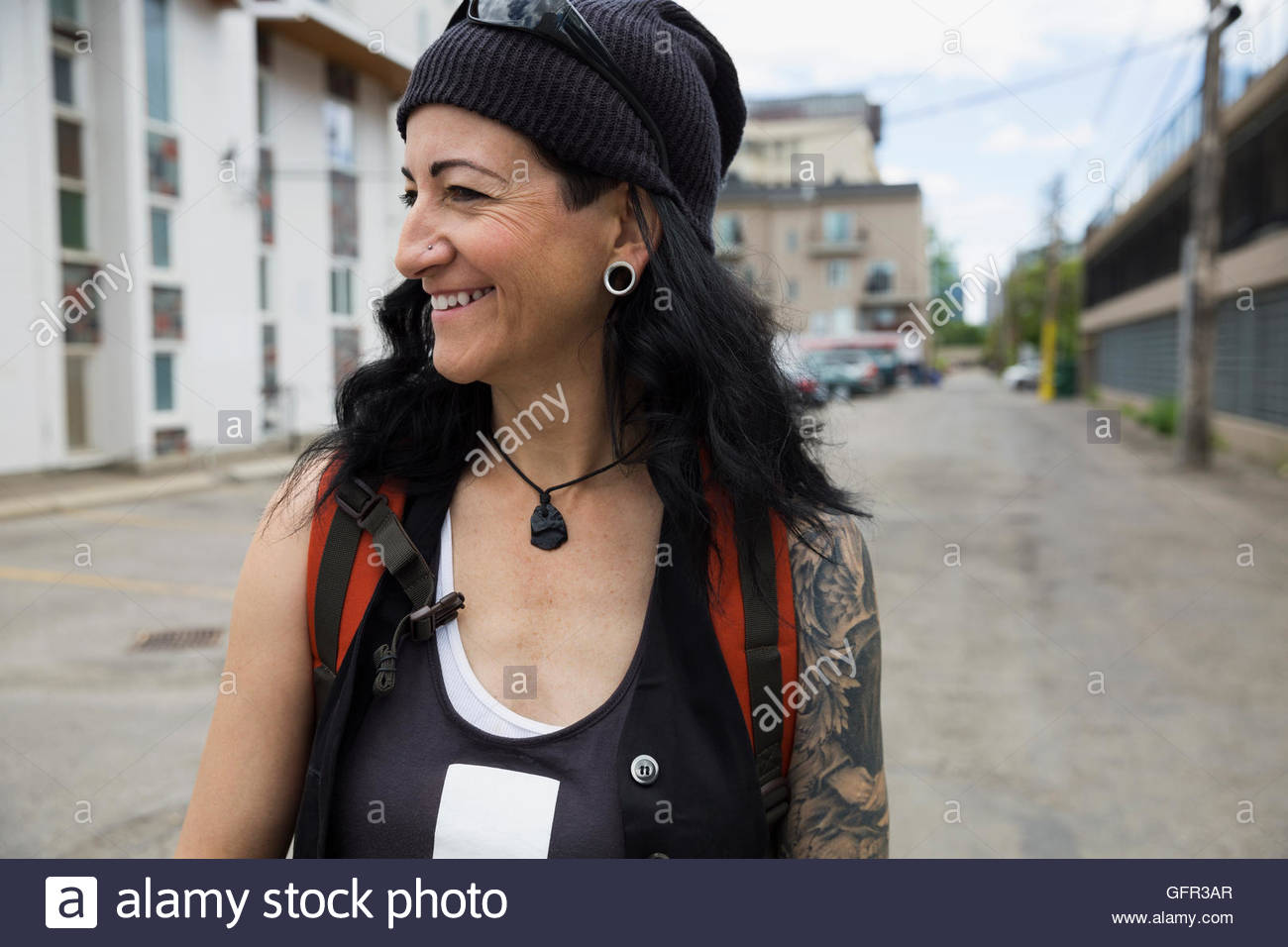 Cool mature woman smiling in urban alley - Stock Image