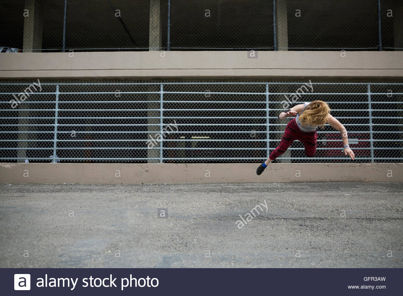 Cool young woman doing parkour against fence in urban alley - Stock Image