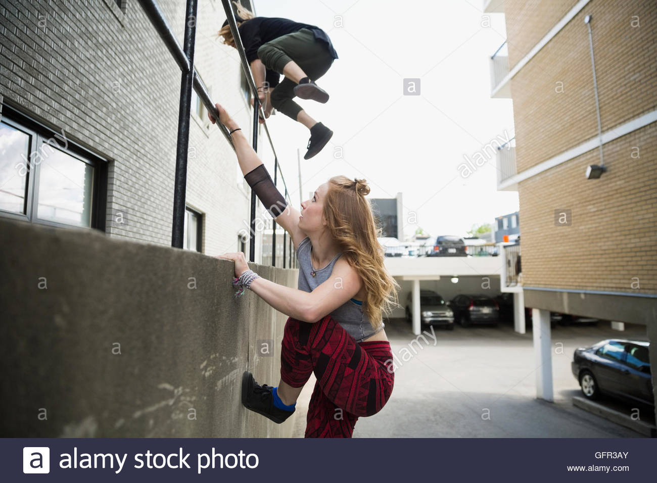 Young man and woman jumping over urban railing - Stock Image