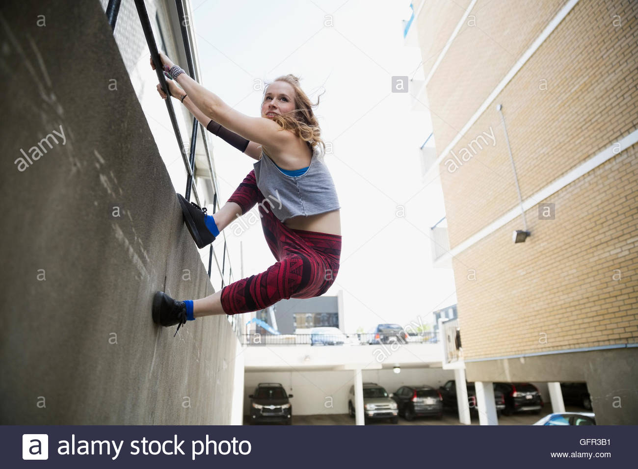 Young woman doing parkour along urban wall - Stock Image
